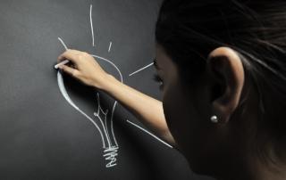 Una bella ragazza disegna una lampadina alla lavagna